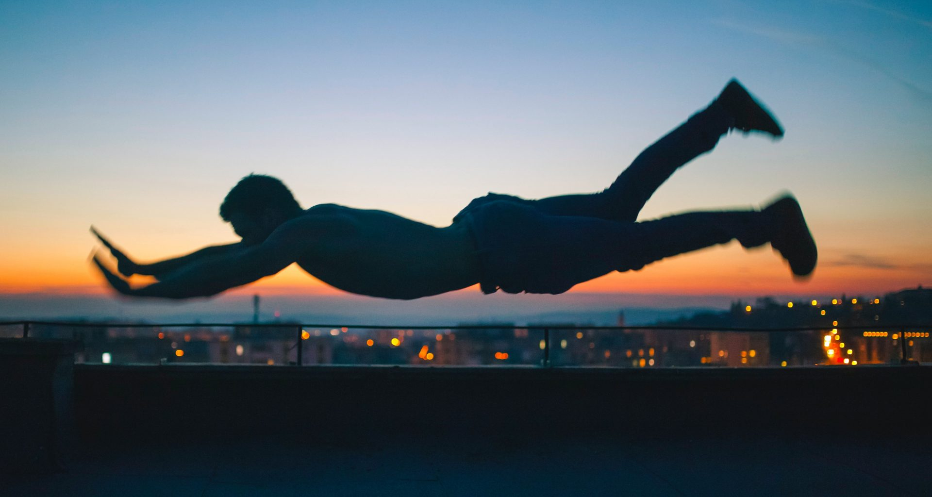 gray scale photo of man falling during golden hour