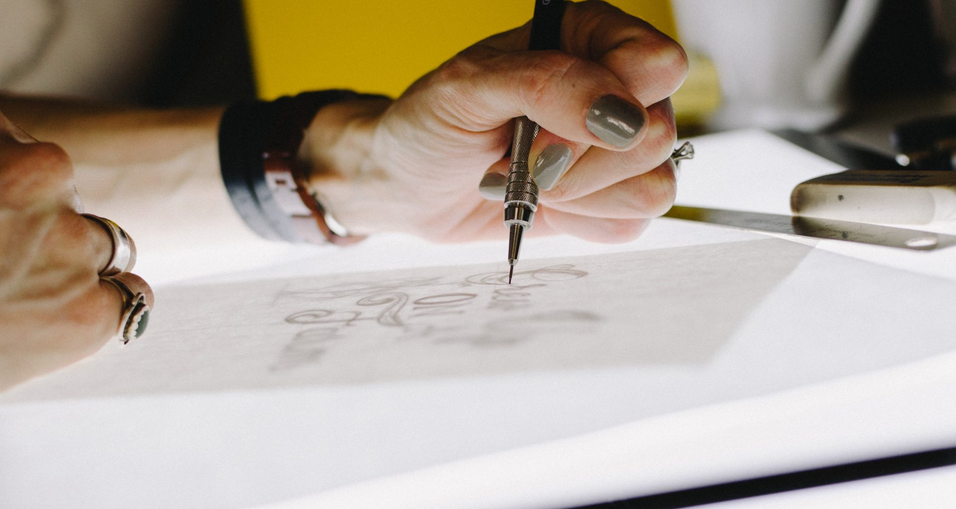 person lettering on tracing paper using mechanical pencil